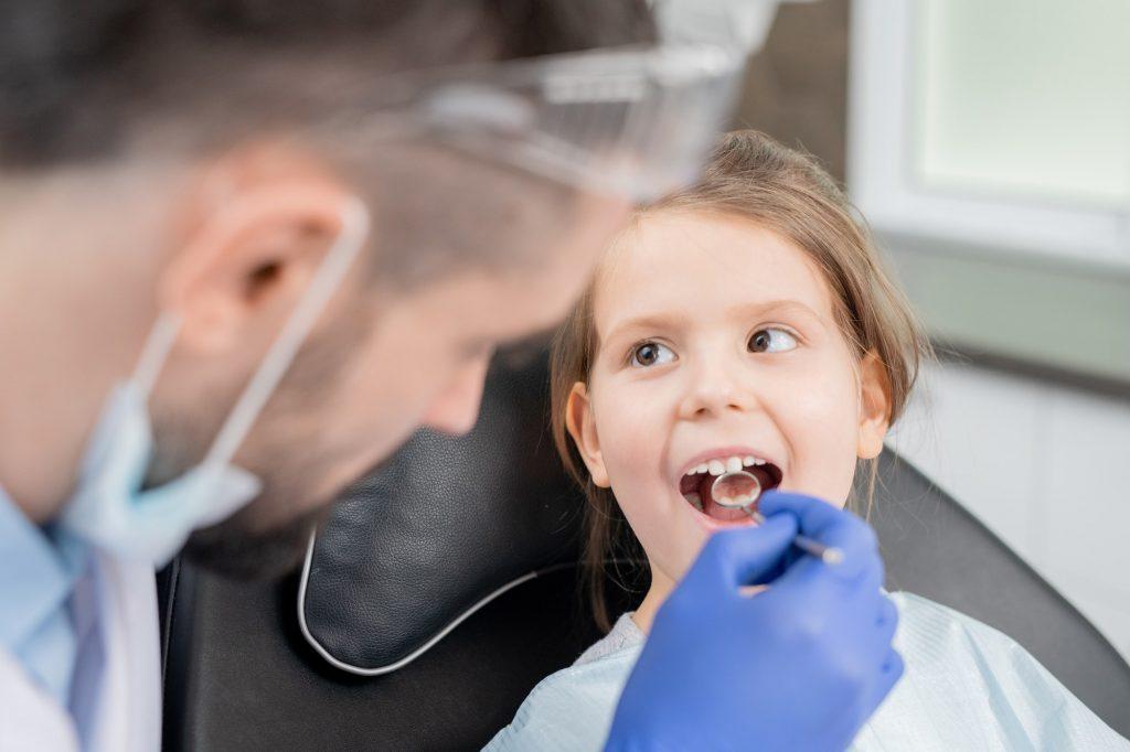 Bambina sorridente durante la sua prima visita dal dentista