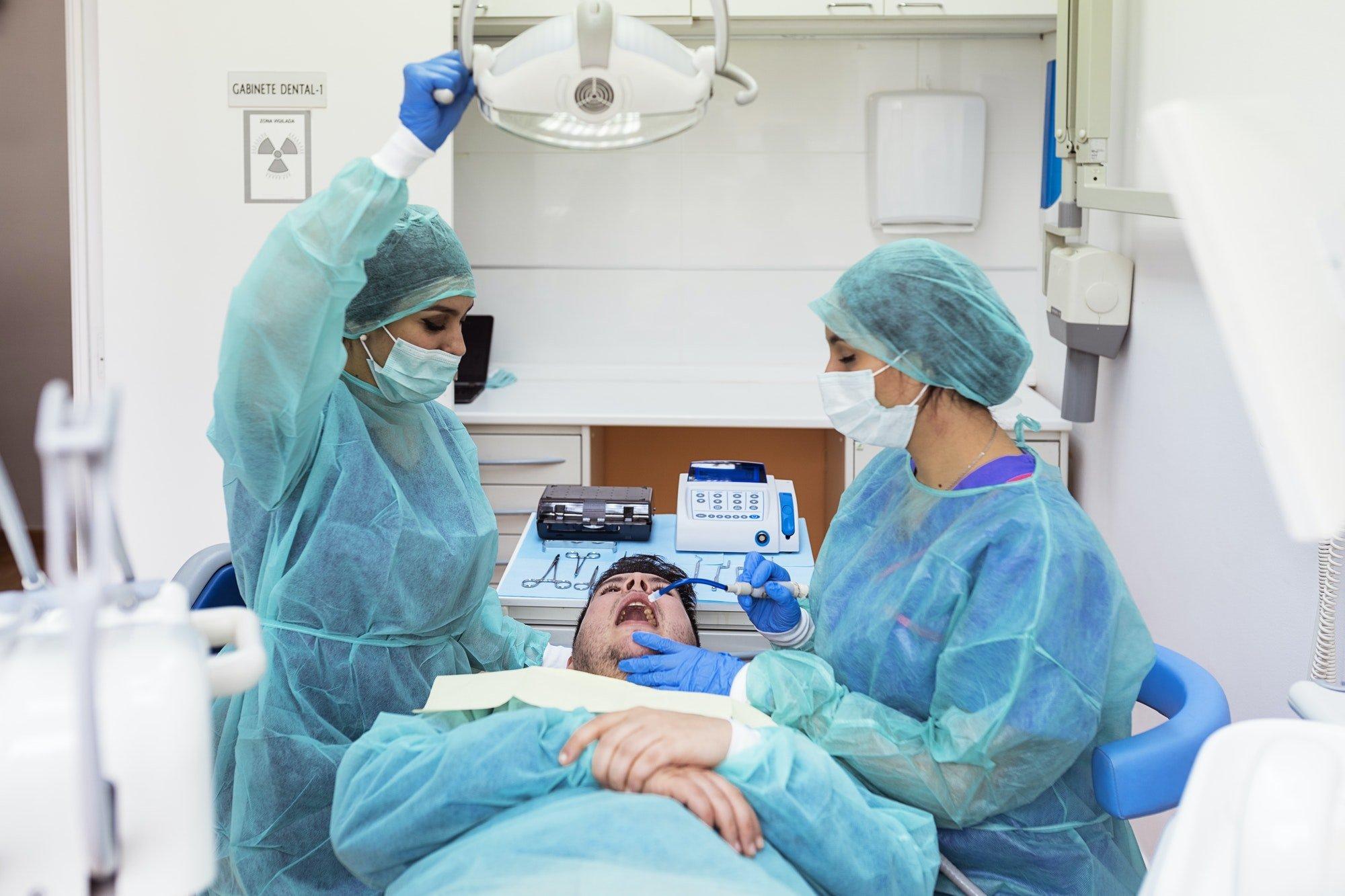 Chirurghi maxillo-facciali in ambulatorio dentistico durante un'innesto osseo