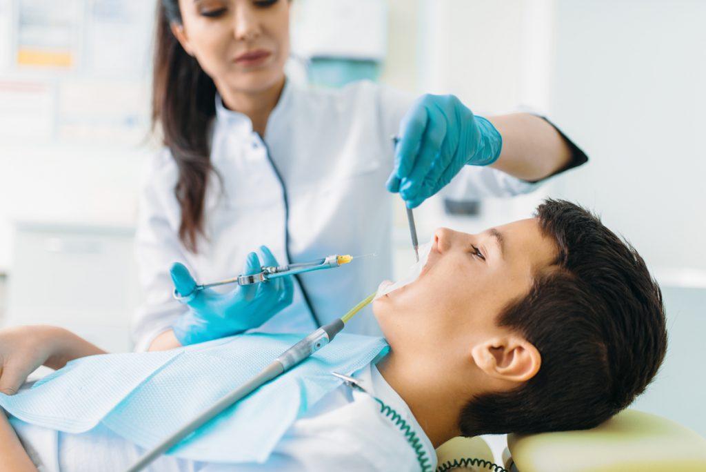 Dentista pratica anestesia locale su paziente bambino