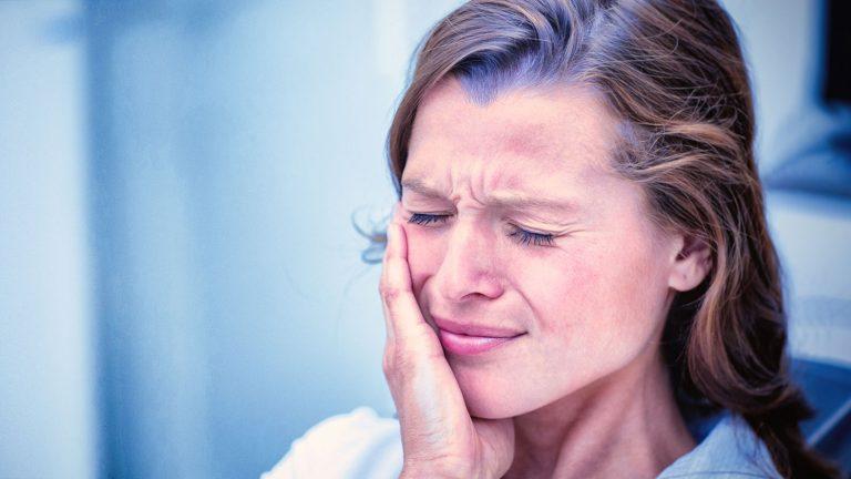 donna con dolore causato da ascesso dentale