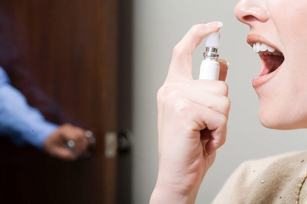 Donna utilizza spray rinfrescante contro l'alitosi